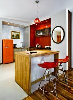 Designer bar stools with red plastic shell seats at counter in open-plan kitchen