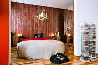 Double bed with bedspread below vintage chandelier and against retro wallpaper