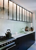 Kitchen counter with marble worksurface, black base units and wall cabinets with glass doors