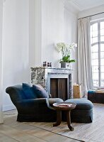 Ethnic-style side table next to blue armchair with matching footstool and scatter cushions in front of fireplace in grand living room with tall latticed windows