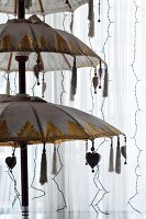 Oriental, tiered parasol lamp and strings of fairy lights decorating white curtain