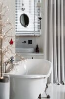 Free-standing bathtub and washstand behind curtain in open-plan interior