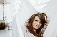 Woman with tousled hair in white hammock in living room