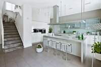 Staircase leading down into modern fitted kitchen with breakfast bar