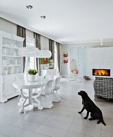 Neo-baroque dining table and postmodern chairs; hanging chair next to fire in fireplace and dog in front of houndstooth chest of drawers