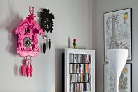 Kitsch cuckoo clocks next to CD shelves with antique finish and drawing of Eiffel Tower