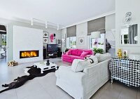 Pink sofa, pale sofa and houndstooth chest of drawers in large interior with cow skin rug and dog in front of fire in fireplace