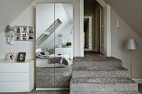 Steps covered in long-pile carpet in silver grey bedroom; bed below skylights reflected in mirrored wardrobe doors