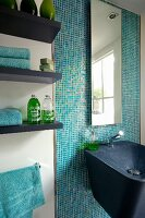 Black composite mineral sink and mirror on wall with turquoise mosaic tiles next to toiletries on floating shelves