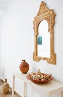 Moroccan mirror above clay pot and collection of seashells on console table
