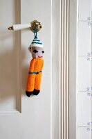Knitted doll on vintage handle of white interior door