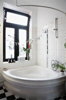 Traditional corner bathtub against tiled wall below window with dark frame