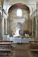 Long, festive dining tables set with white tablecloths in former monastery chapel