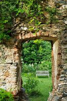Old, climber-covered monastery wall with doorway leading into romantic garden with weathered garden bench