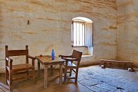 Adobe walled room with rough hewn table and chairs at Mission La Purisima State Historic Park, Lompoc, California
