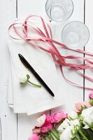 Ranunculus, white paper bags, pen, ribbon and drinking glasses on white wooden surface