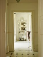 View of lamp on small console table and antique mirror through door