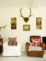 Upholstered chairs with scatter cushions, pictures with hunting motifs and antlers in living room