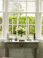 Bouquet and ornaments on side table below window with view of garden