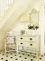 Chair with cushion, lamp and vase of flowers on white-painted chest of drawers and wall mirror below wooden staircase in hall