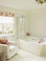 Bright bathroom with bathtub, white upholstered armchair and white wooden floor