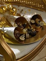 Pretty paper cones of chocolate-shaped decorations and gold baubles on antique chair