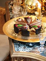 Ornamental cake slices on a brass tray next to crystal glasses on an antique table with a stone top