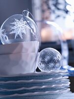 Transparent glass Christmas baubles on stack of plates