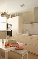 Pale beige, contemporary fitted kitchen and small, white breakfast table and upholstered bench