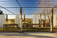 Rustic wooden tables beneath large pergola with wooden supports and white curtains against Mediterranean landscape