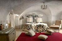 Vaulted room with antique armchair and cushions on red rug in front of twin bathtubs with surround made of boulders
