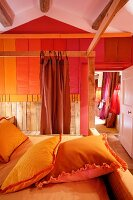 Pillows in yellow pillowcases on four-poster bed with wooden frame opposite wall with stripes of various shades of red in rustic bedroom