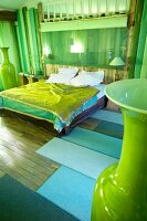 Double bed with green bedspread in rustic bedroom with tall, green floor vases
