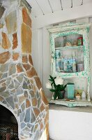 Stone-clad fireplace and chimney breast next to small vintage cabinet mounted on white wooden wall