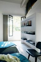 Guest room with white fitted shelving unit in front of open terrace door