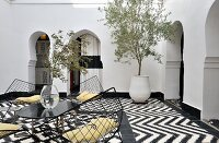 Table and wire shell chairs on black and white tiled floor with zigzag pattern in Moroccan courtyard