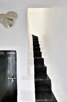 Masonry staircase with black painted runner; wooden door with Moroccan metal fittings and hammered metal dishes on wall