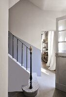 Wrought iron staircase balustrade in simple foyer of house