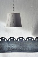 Simple lampshade and perforated metal band as minimalist wall decoration