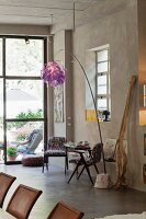 Small table, retro-style chairs and standard lamp with funky purple lampshade in front of floor-to-ceiling French windows in loft apartment