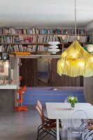 Designer chandelier above dining area; bookcases above kitchen counter with postmodern bar stools; sunken bathtub in background