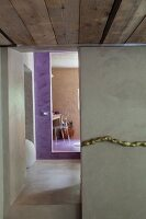 Polished concrete in corridor with violet-painted bathroom entrance at far end; stylised gold cord decorating wall in foreground