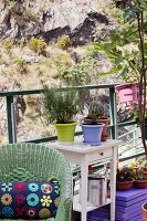 Rattan armchair and potted plants on table on loft-apartment terrace opposite rock face