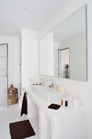 Minimalist white bathroom with large mirror above washstand and dark, contrasting towels