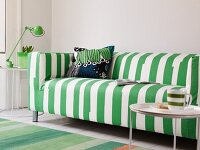 Side table with a cup in front of a modern green and white striped couch in front of a wall