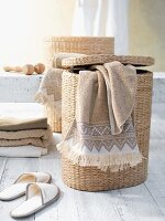 Towel draped over laundry basket next to slippers and stacked towels on white wooden floor