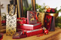 Wrapped presents, gift bags and baubles on rustic wooden table
