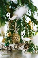 Swan ornaments and baubles hanging from fir branch