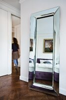 Bed and painting reflected in large, modern wall mirror in bedroom