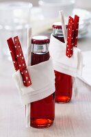 Bottled drinks decorated with napkins & painted clothes pegs